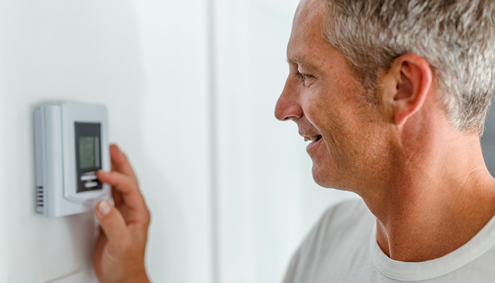 Home owner is shown adjusting his programmable thermostat to control the temperature in his home.